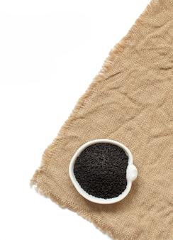Nigella sativa o cumino nero in una ciotola sulla vista superiore della tela da imballaggio isolata su bianco