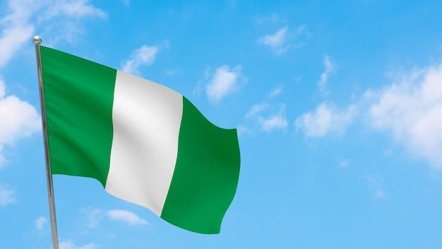 Bandiera della nigeria in pole. cielo blu. bandiera nazionale della nigeria