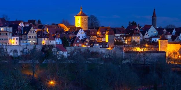 Vista panoramica aerea notturna di tetti, torri e mura della città nel centro storico medievale di rothenburg ob der tauber, baviera, germania meridionale