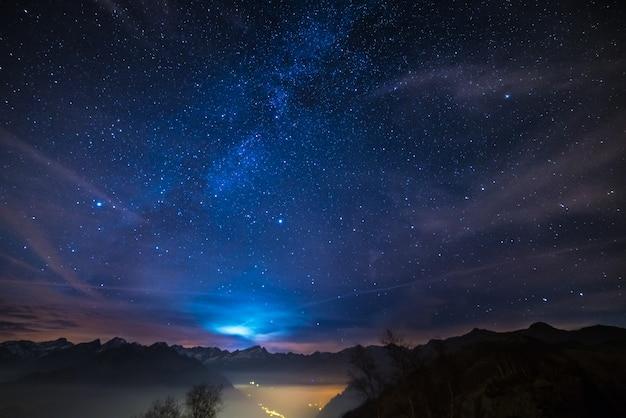 Notte sulle alpi sotto il cielo stellato e la luce della luna sullo sfondo