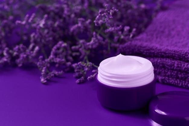 Crema notte antirughe antietà crema per la cura del corpo e cura del viso igiene lozione idratante con fiori viola in barattolo di plastica con asciugamano su sfondo viola.