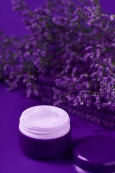 Crema notte antirughe antietà crema per la cura del corpo e del viso igiene idratante lozione con fiori viola in barattolo di plastica con asciugamano sul tavolo.