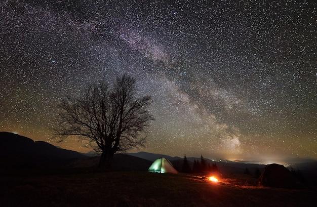 Campeggio notturno nella valle di montagna sotto il cielo stellato
