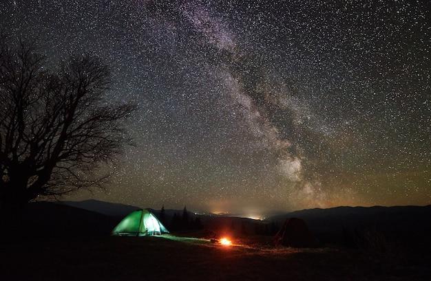 Notte in campeggio nella valle di montagna sotto il cielo stellato
