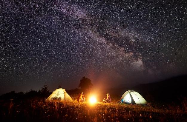 Notte in campeggio in montagna. luminoso falò che brucia tra due viaggiatori con zaino e sacco a pelo, uomo e donna seduti uno di fronte all'altro davanti a tende illuminate sotto un incredibile cielo stellato blu scuro e la via lattea Foto Premium