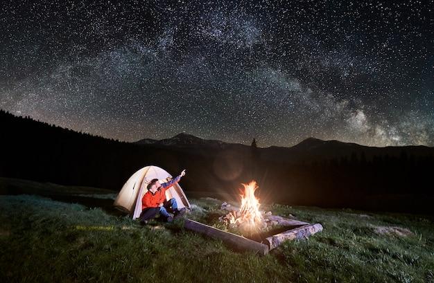 Notte in campeggio in montagna. coppia i turisti seduti nella tenda illuminata vicino al fuoco, guardando il bel cielo notturno pieno di stelle e via lattea. uomo che punta verso il cielo