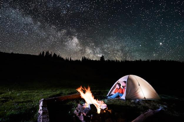 Notte in campeggio in montagna. coppia romantica turisti seduti nella tenda illuminata vicino al fuoco e guardando incredibile cielo notturno pieno di stelle e via lattea