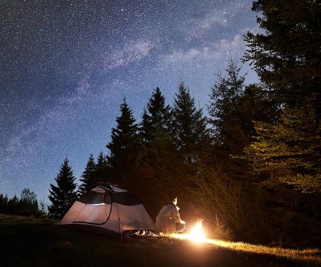 Campeggio notturno in montagna sotto il cielo stellato e la via lattea