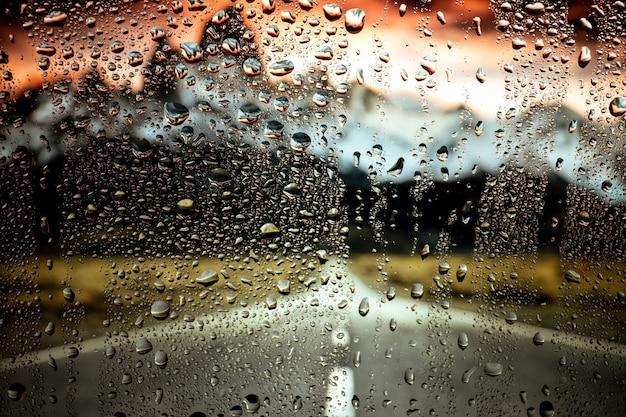 Luci notturne della città attraverso la finestra con acqua piovana e gocce.
