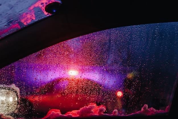 Luci notturne della città attraverso il parabrezza astratto goccia d'acqua sulle luci di vetro e pioggia.