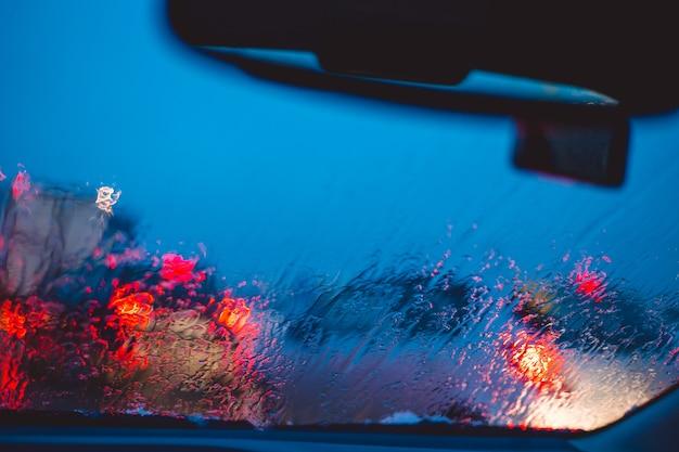 La strada della città di notte attraverso le automobili del parabrezza astraggono la goccia d'acqua del fondo sulle luci e sulla pioggia di vetro.