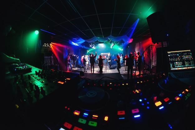 Night club con gente che balla sulla pista da ballo e palco per eventi musicali e mixer dj