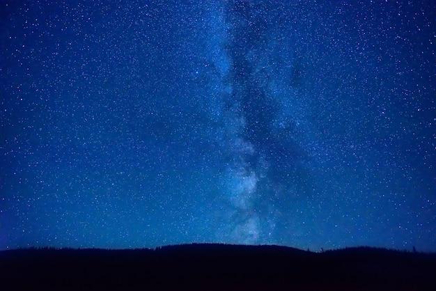 Cielo blu scuro notturno con molte stelle e galassia della via lattea sopra una montagna