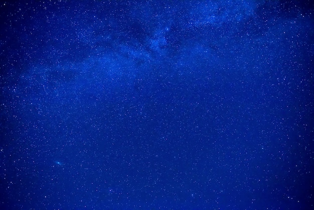 Cielo blu scuro notturno con molte stelle e galassia della via lattea
