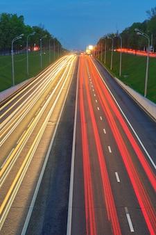 Strada autostradale di notte con luci di automobili. traccia di luci gialle e rosse sulla strada con traffico di velocità. fondo urbano astratto di lunga esposizione