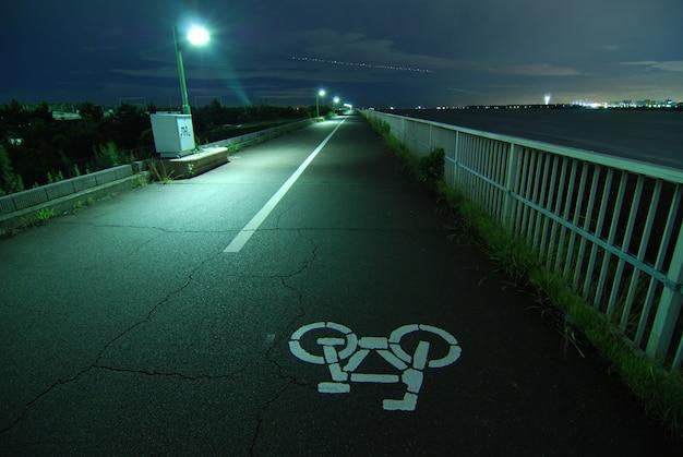 Immagine notturna di una strada ciclabile che va lontano sull'argine della baia di tokyo