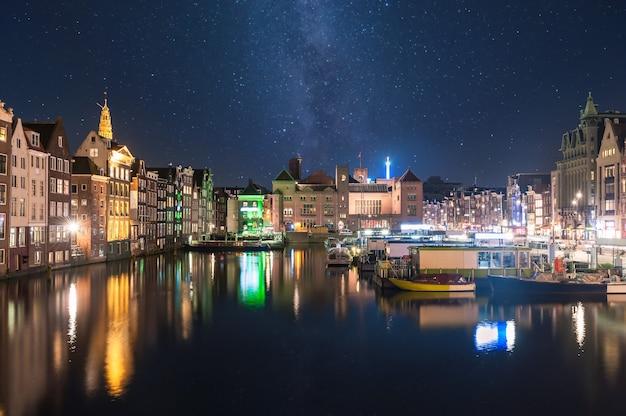 Paesaggio notturno con case e canale ad amsterdam