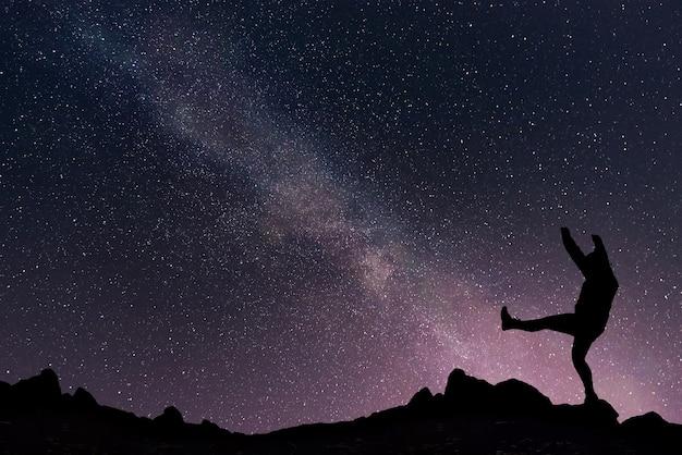 Paesaggio notturno con via lattea sul cielo stellato e ragazza felice sulla cima della montagna.