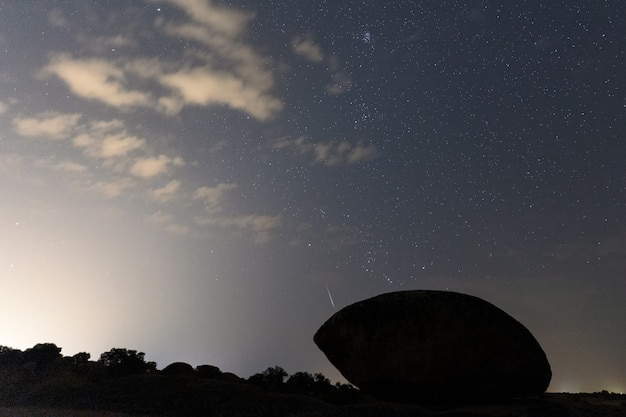 Paesaggio notturno con meteore perseide a barruecos. spagna.
