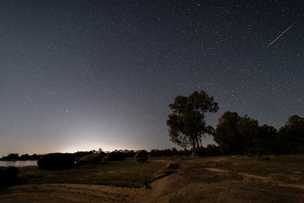 Paesaggio notturno con una stella cadente in valdesalor .. extremadura. spagna.