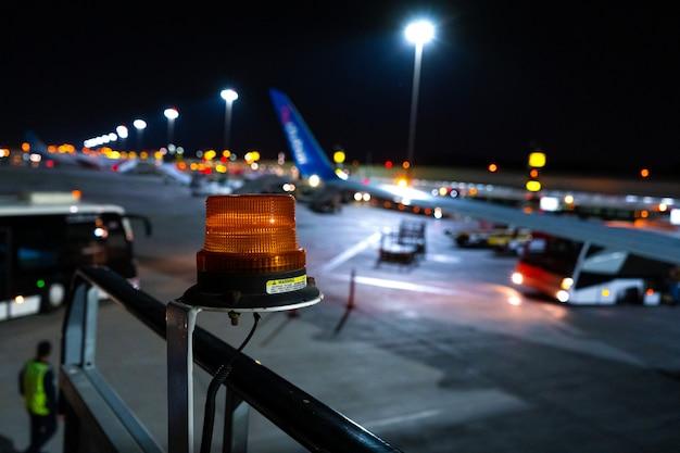 Foto notturna, primo piano, faro giallo per attirare l'attenzione sull'attrezzatura aeroportuale di grandi dimensioni. parcheggio aeronautico offuscato