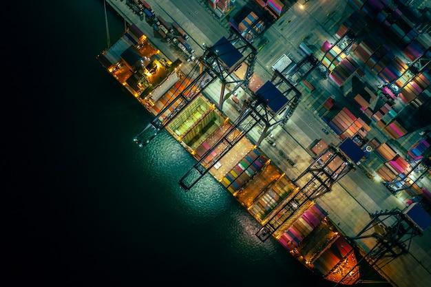 Scena notturna di carico e scarico della nave porta-container nel porto d'altura, vista aerea del servizio aziendale e del trasporto di merci di importazione ed esportazione logistica del carico industriale tramite nave portacontainer in mare aperto,