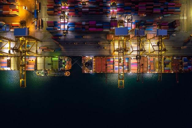 Scena notturna carico e scarico di navi portacontainer nel porto di acque profonde vista aerea del servizio aziendale e dell'industria logistica del carico importazione ed esportazione del trasporto di merci tramite nave portacontainer in mare aperto