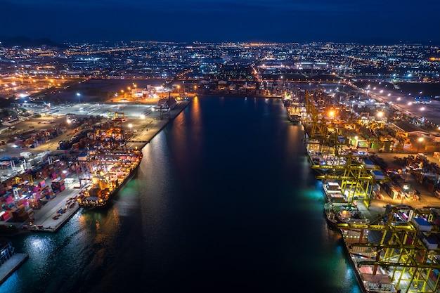 Scena notturna di carico e scarico di navi portacontainer nel porto di acque profonde, vista aerea di servizi aziendali e importazione ed esportazione di merci logistiche di merci industriali