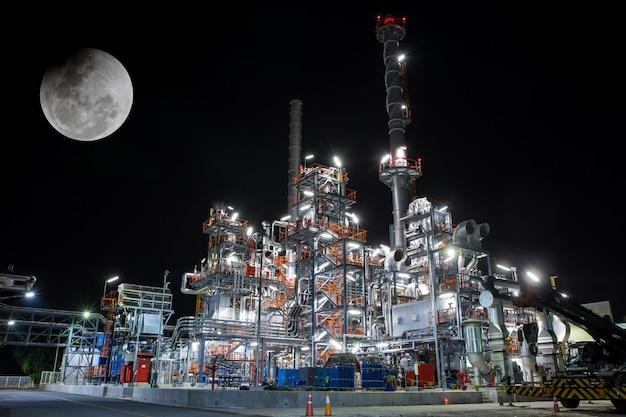 Scena notturna di dettaglio di un impianto industriale chimico pesante con raffineria di tubi in luna piena al crepuscolo