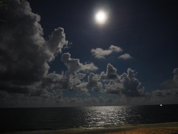 Cielo notturno con la luna piena e riflessione nel mare, belle nuvole