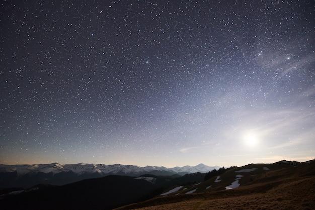 Cielo notturno con stelle che brillano sopra il picco di montagna