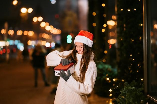 Ritratto di strada di notte di giovane bella donna che agisce entusiasta