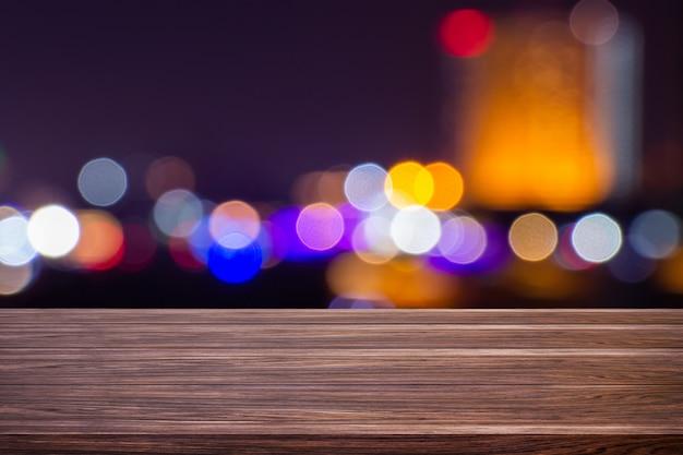 Il bokeh leggero vago penombra di notte a bangkok del centro svuota del fondo di legno scuro dell'estratto della tavola