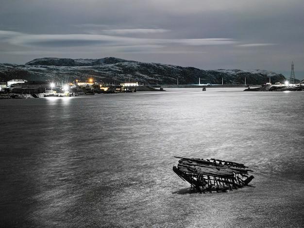 Vista notturna del cimitero delle navi, antico villaggio di pescatori sulla riva del mare di barents, la penisola di kola