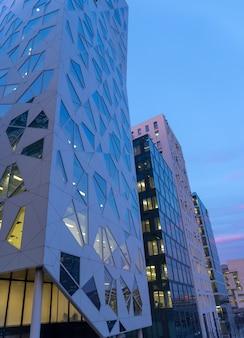 Vista notturna della strada illuminata nel centro degli affari di oslo. architettura moderna in norvegia