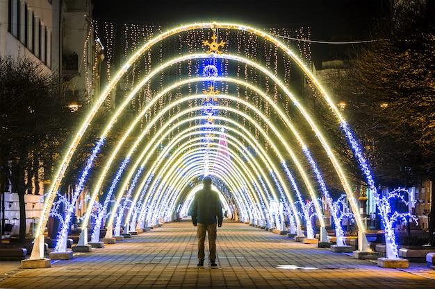 Vista notturna di archi decorativi di capodanno o natale con luci luminose durante le vacanze invernali.