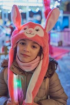 Vista notturna di una ragazza sorridente con un cappello rosa con orecchie illuminate a natale a toledo, spagna