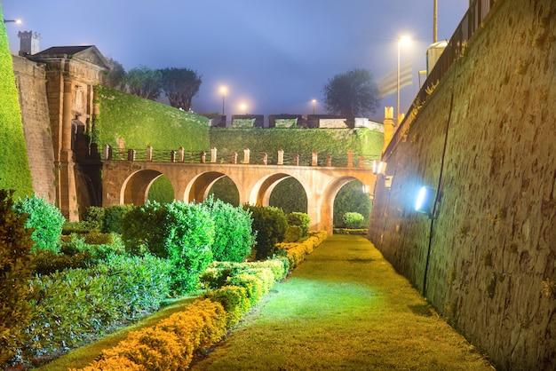 Vista notturna con luce e illuminazione di castillo de montjuic sulla montagna montjuic a barcellona, spagna