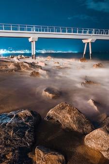 Visione notturna di un ponte sulla spiaggia