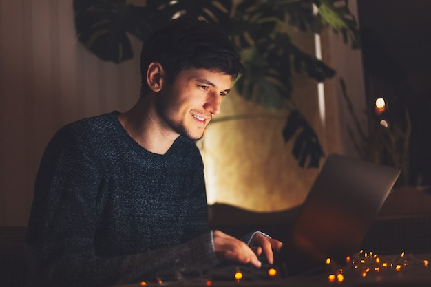 Giovane ragazzo allegro di notte che lavora al computer portatile in camera oscura con ghirlande sul tavolo a casa.