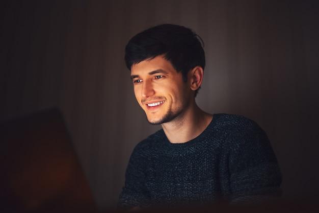 Giovane ragazzo di notte che digita sul computer portatile in camera oscura con ghirlande sulla scrivania a casa.