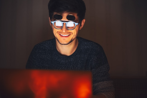 Notte giovane uomo felice con gli occhiali rotondi, guardando nel computer portatile in camera oscura con ghirlande a casa.