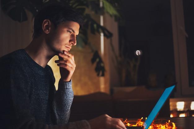 Notte giovane uomo premuroso, toccando il mento, digitando sul computer portatile in camera oscura con ghirlande sulla scrivania a casa.