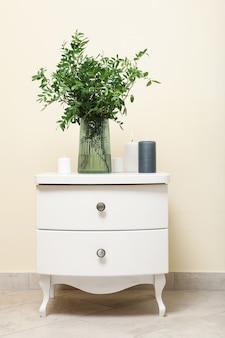 Comodino con vaso con pianta e candele