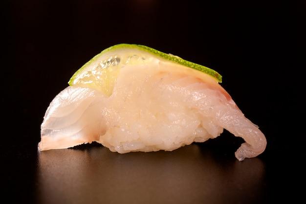 Sushi di nigiri shiromi con il pesce bianco su fondo nero