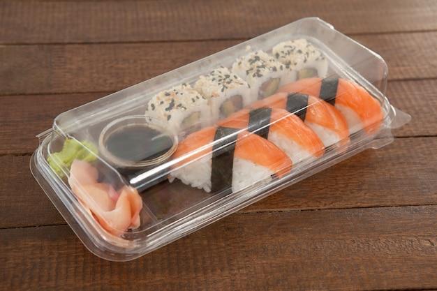 Sushi nigiri e uramaki conservati con salsa di soia in una scatola di plastica