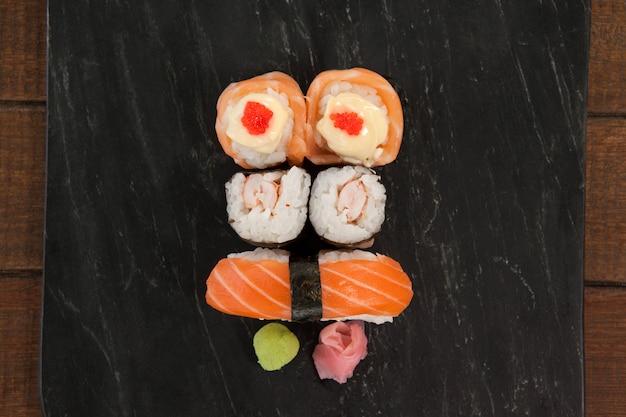 I sushi di uramaki e di nigiri sono servito sull'ardesia di pietra nera sulla tavola di legno