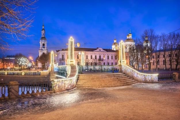 Cattedrale navale di nikolsky a san pietroburgo e ponte krasnogvardeisky sotto il cielo notturno blu