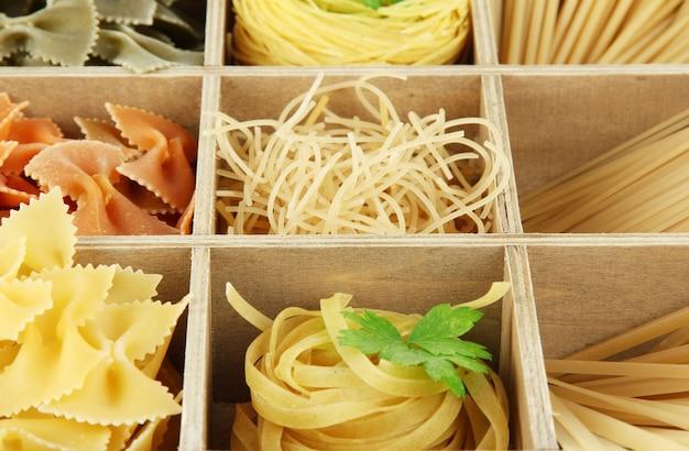Nove tipi di pasta in primo piano di sezioni di scatola di legno