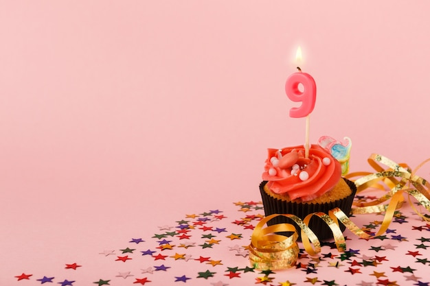 Cupcake per il nono compleanno con candela e codette sprinkle